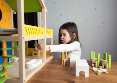 dollhouse: A little girl playing with her dollhouse
