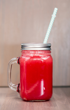 horozontal: A watermelon smoothie in a mason jar with tube on wooden background