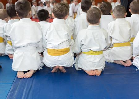 sensei: Children in kimono sitting on tatami on martial arts seminar. Selective focus