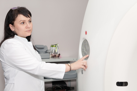 computerised: A female doctor pushing control button on CT scanner. Computerised tomography Stock Photo