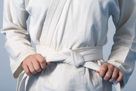 Hands tightening white belt on a teenage dressed in kimono for martial arts