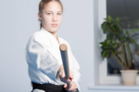 A girl in black hakama standing in fighting pose with wooden  jo stick on white background. Selective focus on stick