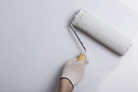 Gros plan du peintre peinture à la main un gris mur avec un rouleau à peinture