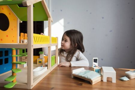 A little girl playing with her dollhouse