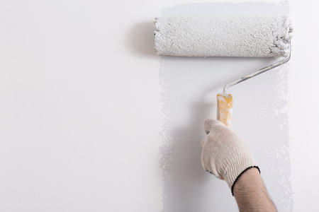 roller: Close up of painter hand painting a wall grey with paint roller