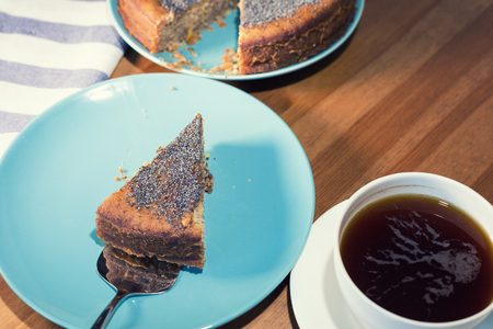 lemon cake: A piece of a lemon cake served with a cup of coffee