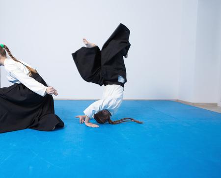 sensei: Two girls in black hakama practice Aikido on martial arts training. Safe falling Stock Photo