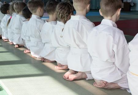 sensei: Group of children in kimono sitting on tatami on martial arts training seminar. Selective focus Stock Photo