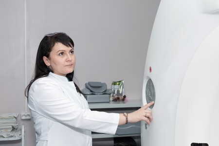 computerised: A brunette female doctor pushing control button on CT scanner. Computerised tomography Stock Photo
