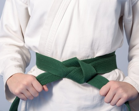 sensei: Hands tightening green belt on a teenage dressed in kimono