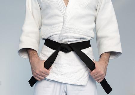 tightening: Martial arts Master tightening black belt Stock Photo