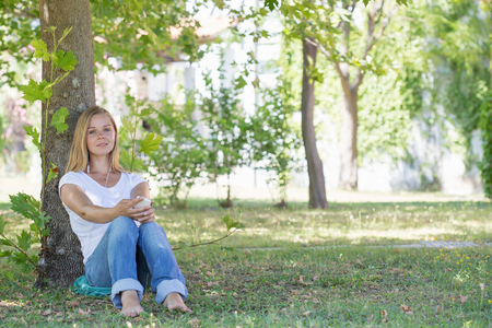 net surfing: A beautiful blonde woman in a park and surfing in the net with her smartphone