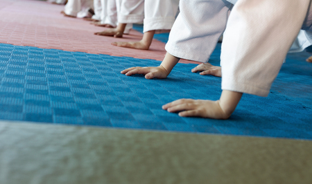 sensei: Group of children in kimono pushing-ups from the tatami on martial arts training. Selective focus