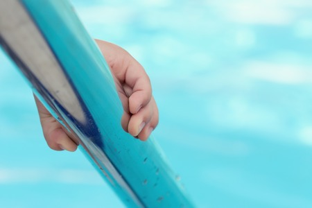 Childs hand holding a handrail in swimming pool.
