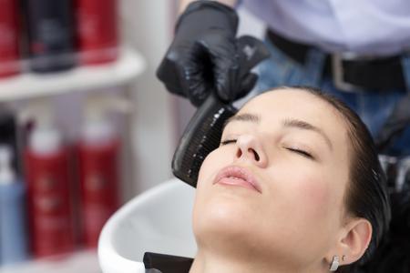 Leuke brunette vrouw haar te wassen in haar studio Stockfoto