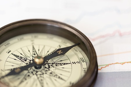 A compass on charts. A direction of successful investment