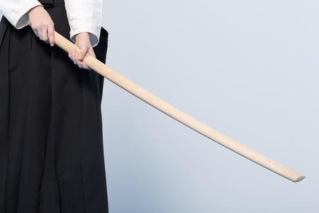 A girl in black hakama standing in fighting pose with wooden sword bokken