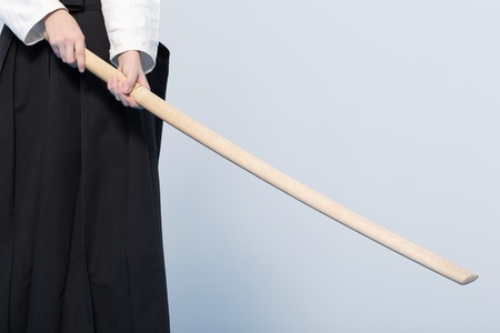 A girl in black hakama standing in fighting pose with wooden sword bokken
