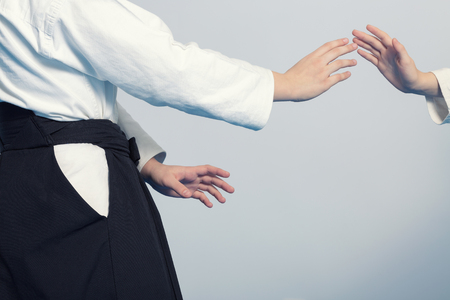 sensei: Hands of two girls standing in stance on martial arts training. Stock Photo