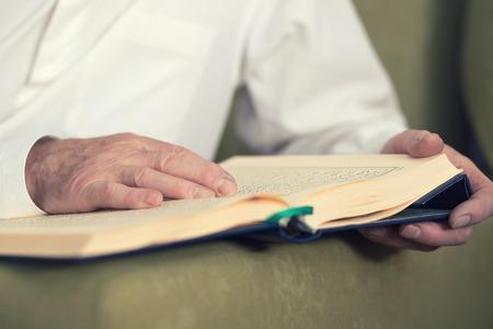 koran: An old man hands holding the Koran