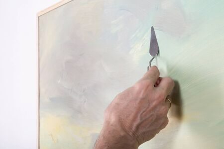 palette knife: An artist painting with a palette knife in studio