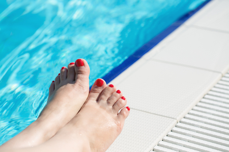 standing stone: Bare female feet at swimming pool side