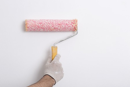 red paint roller: Close up of painter arm painting a wall with red paint roller