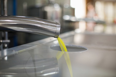 Oil is pouring from the tube at a cold-press factory after the olive harvesting in one of the cretan villages, Greece