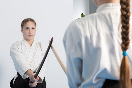 Two girls have their sword practice on Aikido training on white background