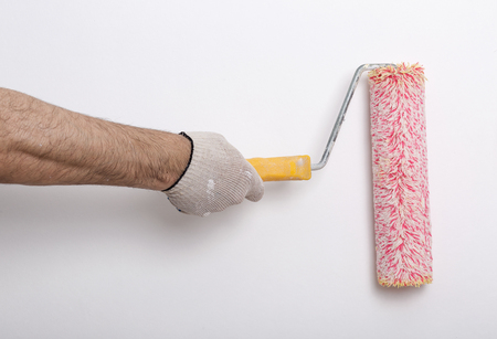 Close up of painter arm painting a wall with red paint roller