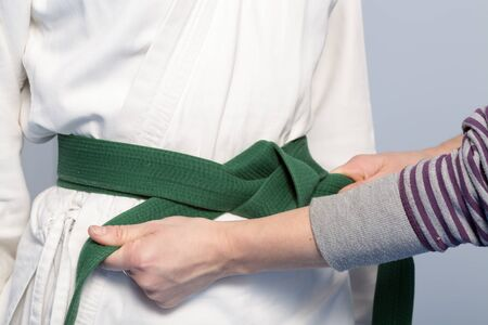 sensei: Hands of a parent who helps a child to tie a green belt for martial arts training