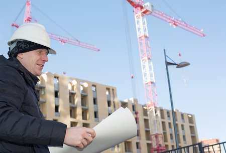An engineer with blueprints in hands on a construction site with cranes