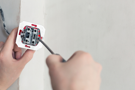 wall socket: Electrician Hands With Screwdriver Installing Wall Socket