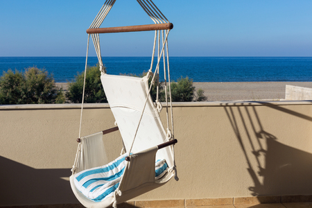 soltería: A swing chair on a balcony with sea view at sunset