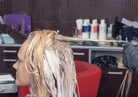 A blonde girl coloring hair in hairdressing salon Stock Photo