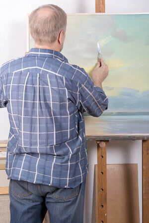 An artist painting in studio with a palette knife Stock Photo
