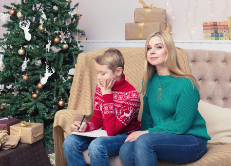 Happy mother and her son writing letter to Santa on Christmas decorations
