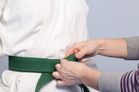 sensei: Hands of a parent who helps a child to tie a belt