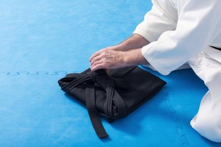 A martial arts master with black belt folding his hakama