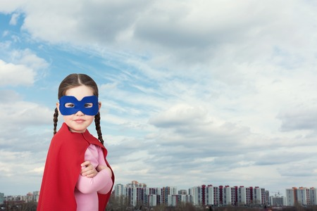 child protection: Cute little super hero girl in the red cloak against the urban background Stock Photo