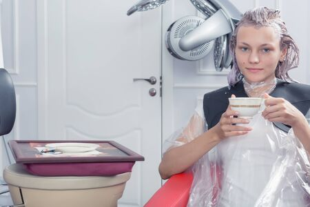 A blonde female dying hair in hairdressing salon 版權商用圖片