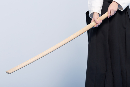 A person in black hakama standing in fighting pose with wooden sword bokken