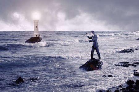 Businessman looking through a telescope against stormy sea with lighthouse