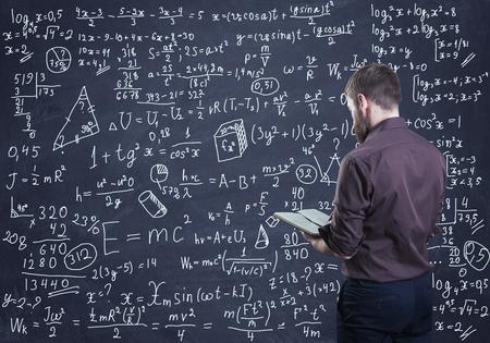 Ein Mann denkt darüber nach, wie man ein mathematisches Problem löst Standard-Bild