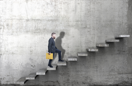 Side view of a man climbing up the steps in a blank concrete wall. 3d render