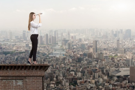 Beautiful woman on a roof top looking through a telescope at a city