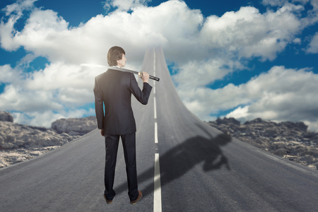 Businessman with katana sword standing on road that goes up to the sky Stok Fotoğraf