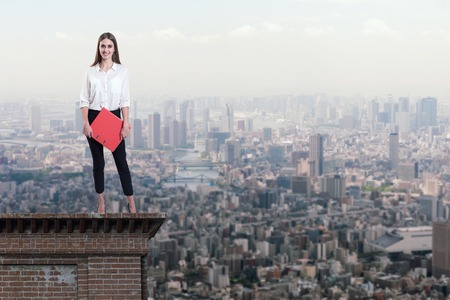 Beautiful businesswoman standing on the rooftop of a skyscraper over a city Zdjęcie Seryjne