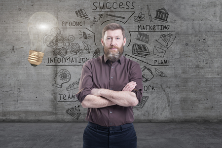 Handsome businessman against a concrete wall with sketch drawn on it and bright lightbulb