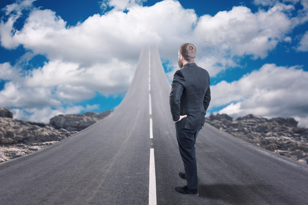 Businessman standing on road that goes up to the sky